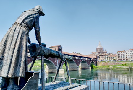 The laundress statue on the bank of the river Ticino with the city on the background in Pavia, Italy. HDR effect. Stock Photo