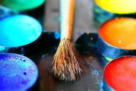 Watercolors palette with a brush. Tilt-shift effect applied.