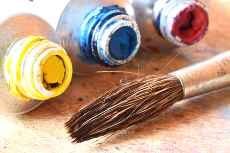 A paint brush near three little tubes (yellow, red, blue)
