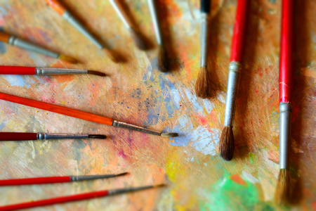 Many paint brushes on a dirty palette. Tilt-shift effect applied.