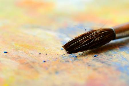 The tip of a paint brush on a palette (macro). Tilt-shift effect applied.
