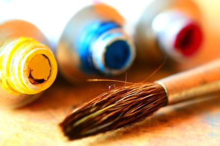 A paint brush near three little tubes (yellow, red, blue). Tilt-shift effect applied.