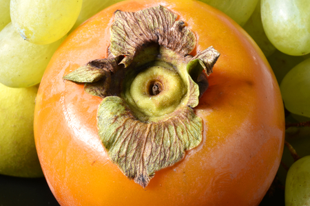 An orange persimmon with some white grapes: typical Italian autumn fruits.