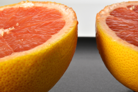 Two half of pink grapefruit with black background