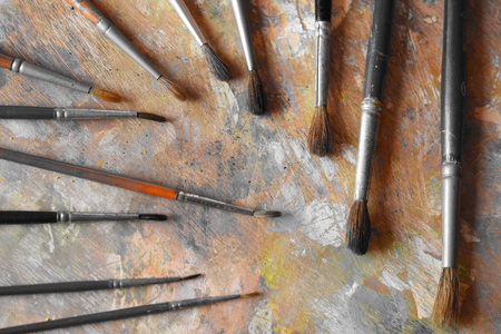 Many old paint brushes on a dirty palette Stock Photo