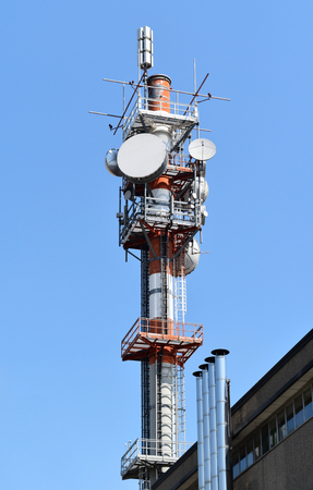A tall white and red antenna on blue sky Banco de Imagens
