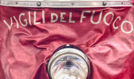 """TURIN, ITALY, CIRCA FEBRUARY 2018: detail of the written """"vigili del fuoco"""" (Italian National Firefighters Corps) on a motorbike on red background. HDR effect."""