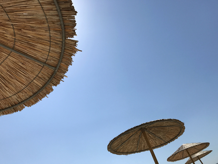 Straw umbrellas on blue sky in a sunny day on a beach. Suitable to be used like a background. Stock Photo