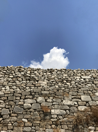 An ancient wall made with many stones, with blue sky and a white cloud in a sunny day. Stock Photo