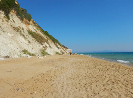 An empty big sandy golden beach with turquoise sea near a cliff in Cephalonia or Kefalonia in Greece.