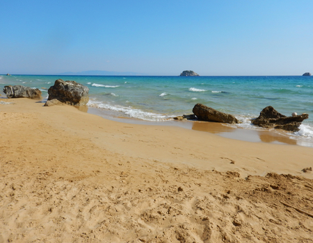 An empty big sandy golden beach with turquoise sea in a sunny day in Cephalonia or Kefalonia in Greece.