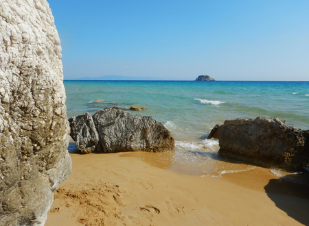 Big stones on a sandy golden beach with turquoise sea in a sunny day in Cephalonia or Kefalonia in Greece.
