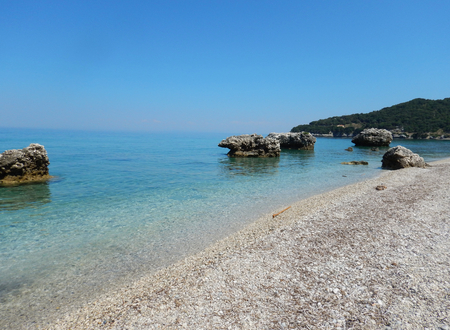 An empty white stone beach with transparent turquoise sea and rocks in Cephalonia or Kefalonia in Greece.