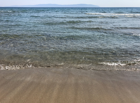 Seaboard with transparent sea, sand and waves in summertime. Stock Photo