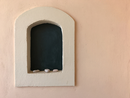 A little recess with arch, shells and black background on a pale pink wall. Copy space.