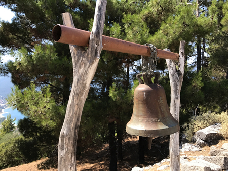 An old metal small bell on a wooden perch in a forest in a sunny day.
