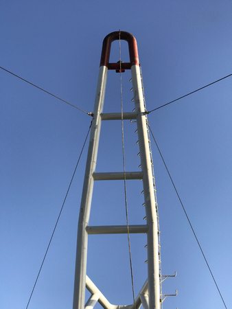 A white metallic mast of a boat with limpid blue sky in the background. Stock Photo