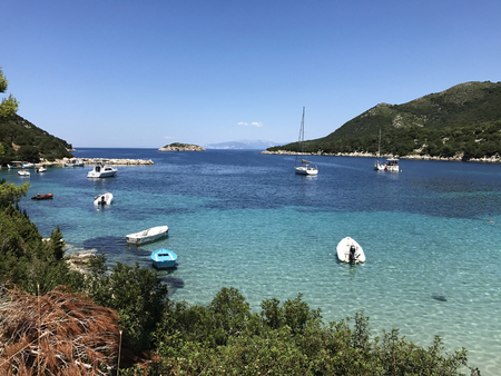 Boats on the turquoise sea of Atheras beach in Cephalonia or Kefalonia, Greece