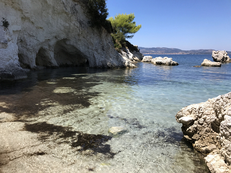 A little bay with turquoise water and white cliff in a sunny day in Cephalonia or Kefalonia in Greece. Stock Photo