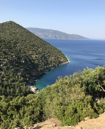 A bay of Kefalonia in Greece, with blue sea and wild green forest on the mountain. Stock Photo