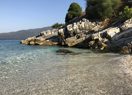 The turquoise and transparent sea of the coast of Kefalonia in Greece with white rocks. Stock Photo