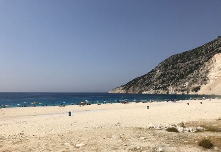 Myrtos beach with its white sand, blue sea, many tourists and umbrellas, in Cephalonia or Kefalonia in Greece. Stock Photo