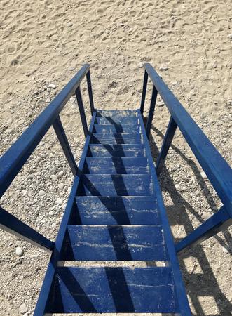 Steps of a wooden blue lifeguard tower on a sandy beach.