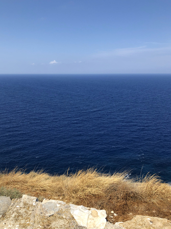 Very blue sea and limpid sky with dry grass in a Greek island: summer background.
