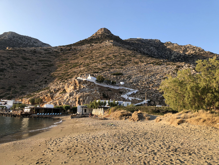 Kamares golden beach at sunset with mountains and a church in the background, in Sifnos island in Greece. Stock Photo