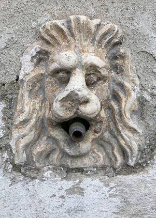 An ancient stone fountain with a lion face. Stock fotó