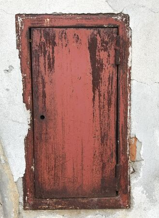 A old red wooden door on a white ancient wall