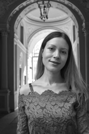 Portrait of a beautiful young woman with long hair and a lace dress with an Italian stone and marble neoclassical palace entrance in the background. Black and white. Banco de Imagens