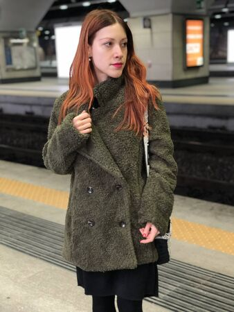 Portrait of a beautiful young woman with long copper hair and a green coat traveling and waiting a train near rails in a modern station underground.
