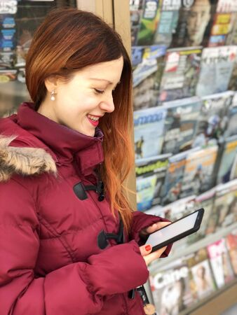 Portrait of a beautiful young woman with long copper hair and a red coat reading on a ereader with a newsstand or a kiosk in the background.