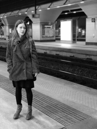 Portrait of a beautiful young woman with long hair traveling and waiting a train near rails in a modern station underground. Black and white.