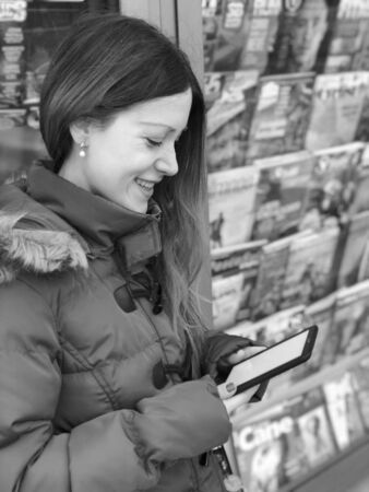 Portrait of a beautiful young woman with long copper hair and a red coat reading on a ereader with a newsstand or a kiosk in the background. Black and white. Stock fotó