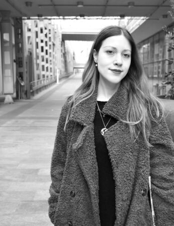 Portrait of a beautiful young woman with long hair and a coat smiling in a modern urban background. Black and white.