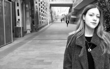 Portrait of a beautiful young woman with long hair and a coat thinking in a modern urban background. Black and white, copy space.