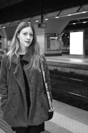 Portrait of a beautiful young woman with long hair and a coat near rails in a modern station underground. Black and white. Stock fotó
