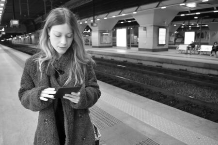 Portrait of a beautiful young woman with long hair and a coat reading on a ereader and waiting a train near rails in a modern station underground. Black and white.