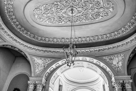 Detail of an Italian stone and marble neoclassical ceiling in a palace in city center in Italy. Black and white.