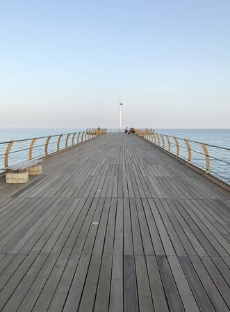 a wooden platform on the sea on a sunny day with blue sky at sunset