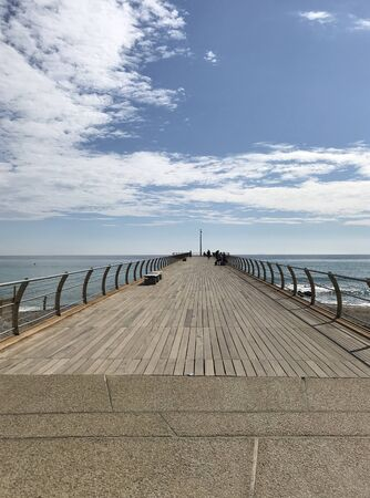 a wooden platform on the sea on a sunny day with blue sky and white clouds