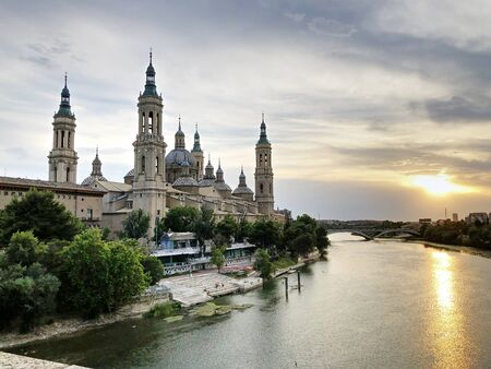 The Cathedral-Basilica of Our Lady of the Pillar, a Roman Catholic church in the city of Zaragoza, in Aragon, Spain, on river Ebro seen by the Old Stone bridge at sunset
