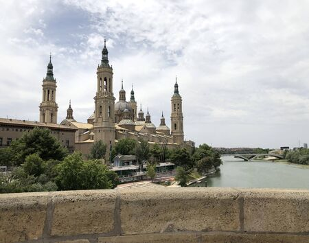 The Cathedral-Basilica of Our Lady of the Pillar, a Roman Catholic church in the city of Zaragoza, in Aragon, Spain, on river Ebro seen by the Old Stone bridge Stock Photo