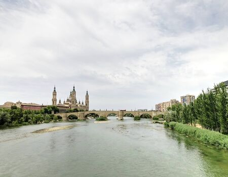 View of the Cathedral-Basilica of Our Lady of the Pillar, a Roman Catholic church on river Ebro and the Old Stone bridge in the city of Zaragoza, in Aragon, Spain. Stock Photo