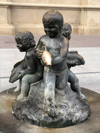A fountain with a dark stone statue of three small children or cherubs