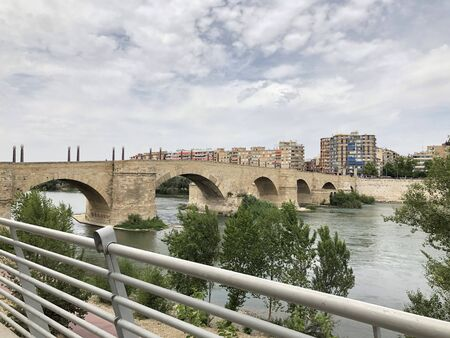 The Ebro river and the old Stone Bridge of Zaragoza in Spain, in a cloudy day Stock Photo