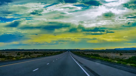 Straight flat asphalt road stretching into the distance beyond the horizon in Utah, USA