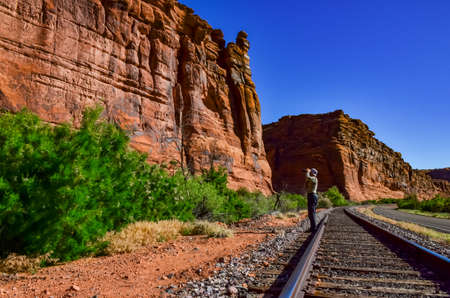 Railroad at the bottom of a canyon next to Layered Geological Formations of Red Rocks. USA